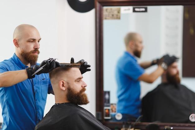 Męski profesjonalny fryzjer obsługujący klienta nożyczkami