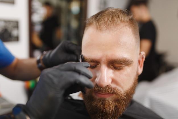 Męski profesjonalny fryzjer obsługujący klienta, strzygący brwi nożyczkami
