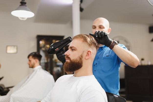 Męski profesjonalny fryzjer obsługujący klienta, suszący włosy suszarką do włosów