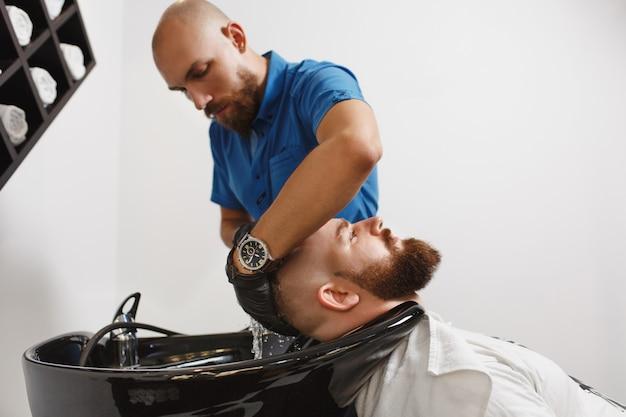 Męski profesjonalny fryzjer obsługujący klientowi głowę myjącą w czarnej modnej umywalce, wycierający ręcznikiem
