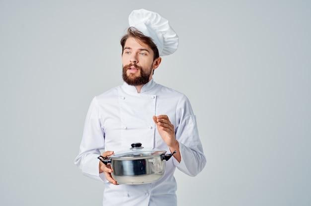 Męski profesjonalny kucharz z rondelkiem w rękach przygotowujący jedzenie w restauracji