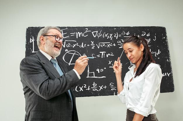 Męski profesor i młoda kobieta przeciw chalkboard w sala lekcyjnej