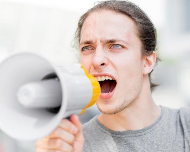 Męski protestujący krzyczy w megafonu zakończeniu