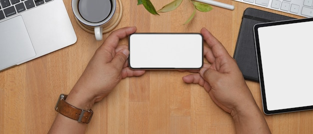 Męski przedsiębiorca wręcza trzymać próbnego smartphone na biurowym biurku z innymi cyfrowymi przyrządami i dostawami