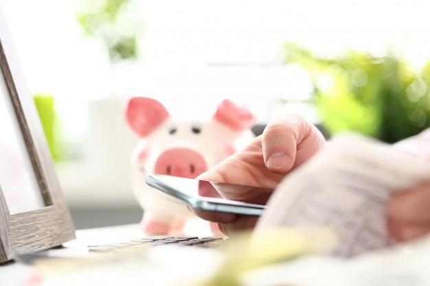 Męski ręka chwyta telefon komórkowy w ręce wypełnia niektóre elektroniczny dokument
