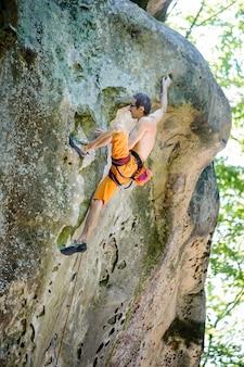 Męski rockowego arywista wspina się z arkaną na skalistej ścianie