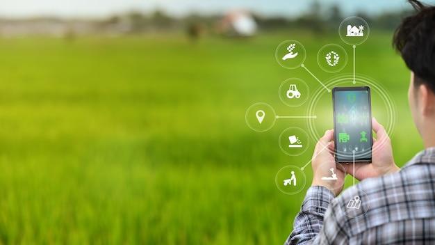 Męski rolnik pracuje w terenie, używając telefonu komórkowego z technologią innowacji do inteligentnego systemu farmy.