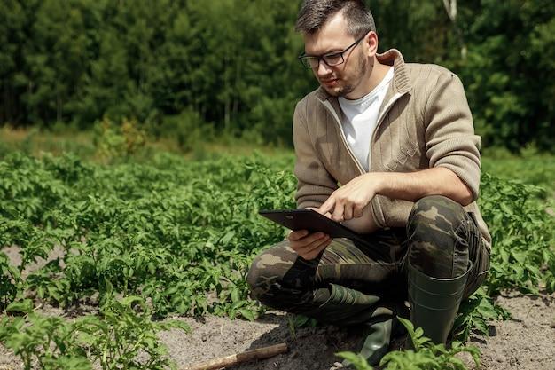 Męski rolnik siedzi w polu i używa pastylkę. nowoczesne zastosowanie technologii w działalności rolniczej.