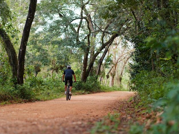 Męski rowerzysta jedzie wiejskie drogi w dżungli. klimat tropikalny. widok z tyłu.