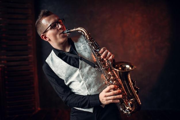 Męski saksofonista grający klasyczny jazz na saksofonie