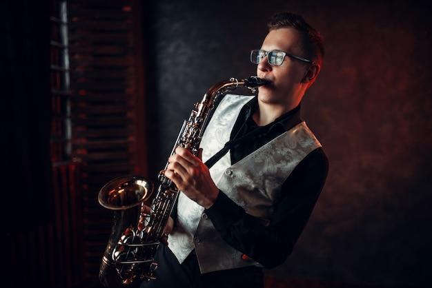 Męski saksofonista grający melodię jazzu na saksofonie