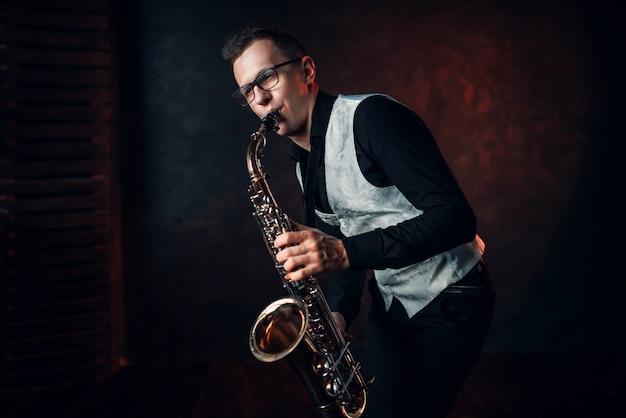 Męski saksofonista grający melodię klasycznego jazzu na saksofonie.