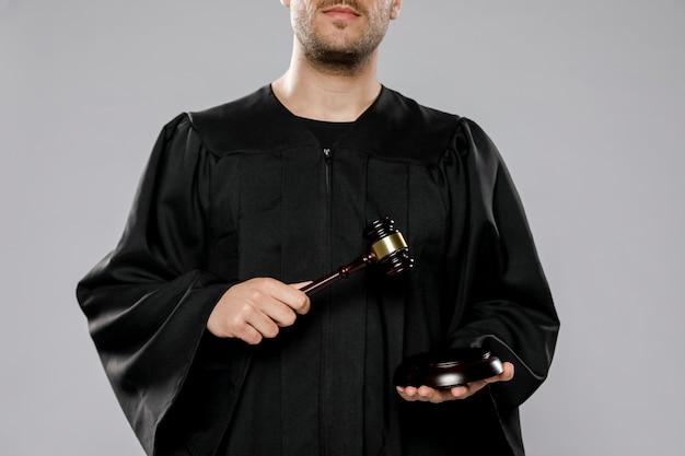Męski sędzia pozuje z młoteczkiem
