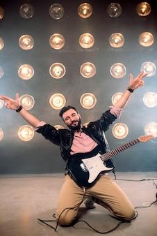 Męski showman z gitarą elektryczną na scenie z dekoracjami świateł.