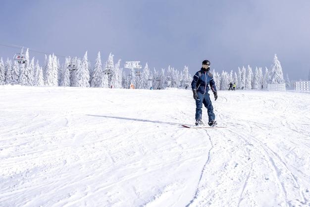 Męski snowboardzista zjeżdżający ze stoku z pięknym zimowym krajobrazem w tle