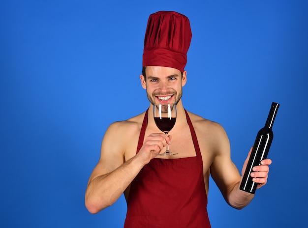 Męski sommelier degustujący czerwone wino, dzięki któremu zawody są szczęśliwe sexy szef kuchni w bordowym kapeluszu kucharza i