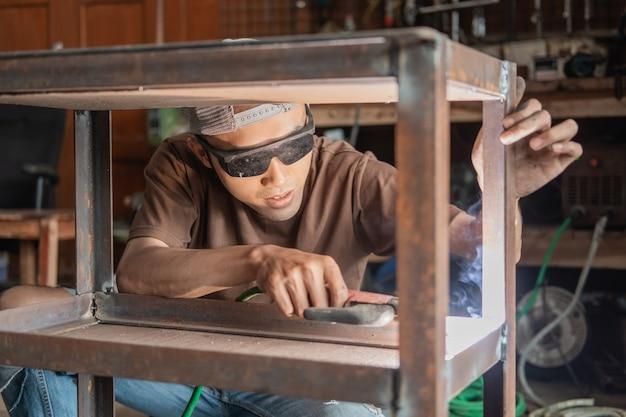 Męski spawacz używa spawania elektrycznego do spawania metalowej ramy na tle warsztatu spawalniczego