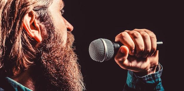 Męski śpiew z mikrofonem. mężczyzna z brodą, trzymający mikrofon i śpiewający. brodaty mężczyzna w karaoke śpiewa piosenkę do mikrofonu. mężczyzna uczęszcza na karaoke