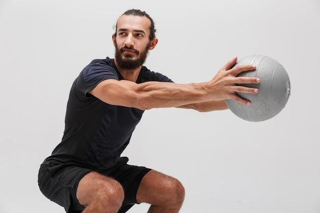 Męski sportowiec brunetka w dresie robi trening z piłką fitness odizolowaną nad białą ścianą