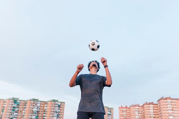 Męski sportowiec ćwiczy z piłki nożnej piłką przeciw niebieskiemu niebu