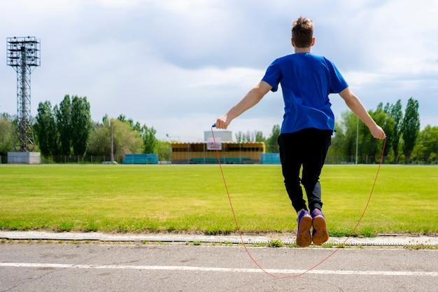 Męski sportowiec sportowiec ćwiczy ze skakanką na stadionach zewnętrznych, zwiększa wytrzymałość