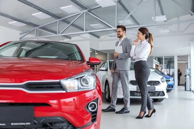 Męski sprzedawca samochodów w garniturze spaceruje po salonie samochodowym z kobietą, która chce kupić samochód i rozmawia o specyfikacji samochodów.