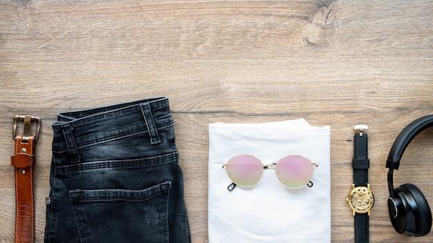 Męski strój na stole, t-shirt, dżinsy, słuchawki, okulary, zegarki i pasek. widok z góry
