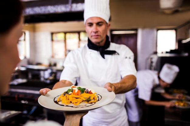 Męski szef kuchni daje talerzowi przygotowany jedzenie kelnerka w kuchni
