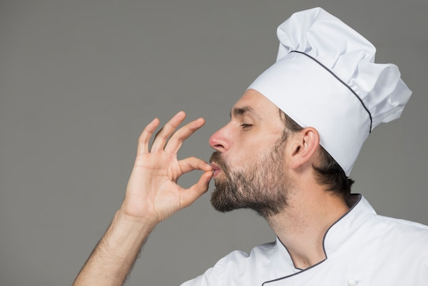 Męski szef kuchni w bielu mundurze robi smakowitemu znakowi przeciw popielatemu tłu