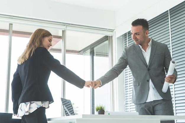 Męski szef pięści garbek z żeńskim pracownikiem dla sukcesu