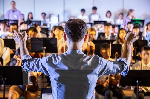Męski szkolny konduktor przewodzi swojemu studenckemu zespołowi, by wykonywał muzykę na szkolnym koncercie
