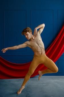 Męski tancerz baletowy, szkolący się w klasie tańca, niebieskie ściany i czerwone sukno. wykonawca o muskularnym ciele, elegancji ruchów