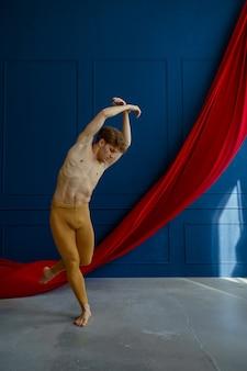 Męski tancerz baletowy, szkolący się w klasie tańca, niebieskie ściany i czerwone sukno. wykonawca o muskularnym ciele, wdzięku i elegancji ruchów