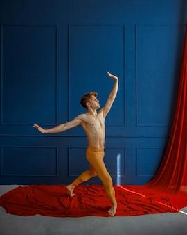 Męski tancerz baletowy, występujący w akcji, studio tańca, niebieska ściana i czerwona tkanina. wykonawca o muskularnym ciele, wdzięku i elegancji ruchów