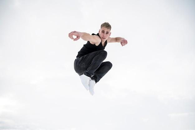 Męski tancerz pozuje podczas gdy w powietrzu