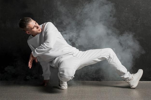 Męski tancerz pozuje z mgłą