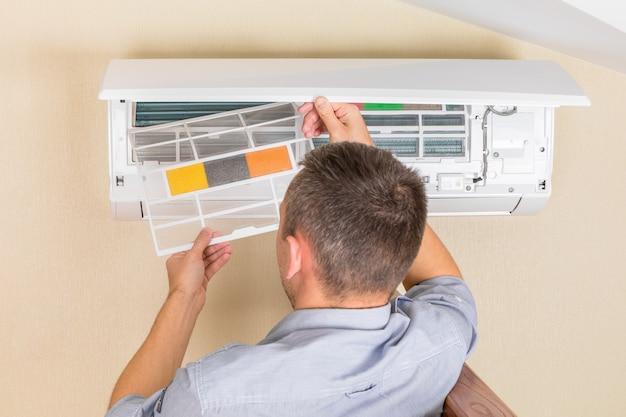 Męski technik czyści klimatyzator indoors