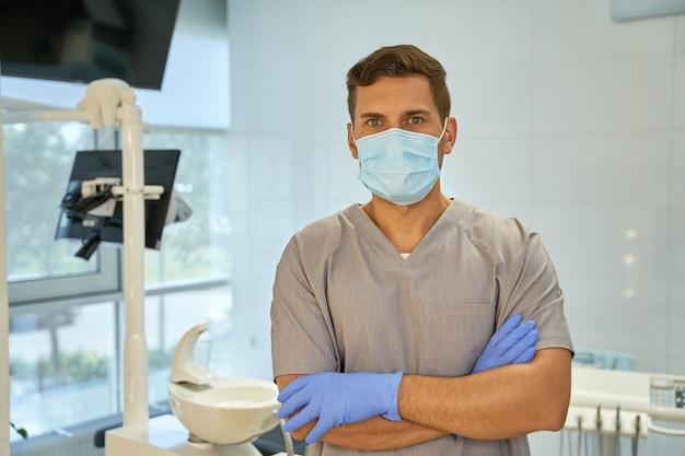 Męski technik dentystyczny noszący maskę i rękawiczki w miejscu pracy