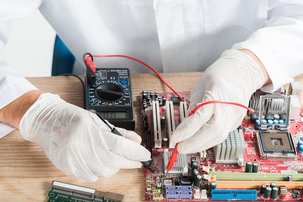 Męski technik egzamininuje komputerową płytę główną z cyfrowym multimeter