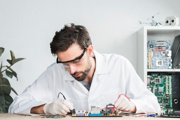 Męski technik egzamininuje łamającego komputer z cyfrowym multimeter
