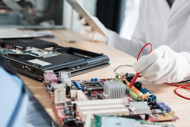 Męski technik egzamininuje macierzystą deskę z cyfrowym multimeter