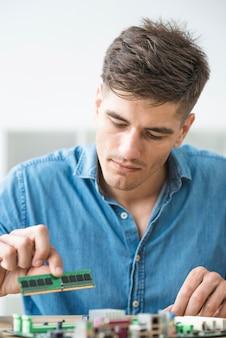 Męski technik instaluje ram na komputerowej płycie głównej