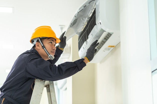 Męski technik naprawia klimatyzator jednolitego bezpieczeństwo indoors.