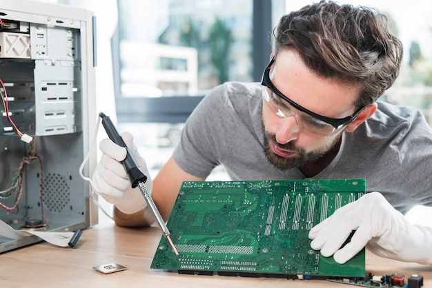 Męski technik naprawia komputerową obwód deskę