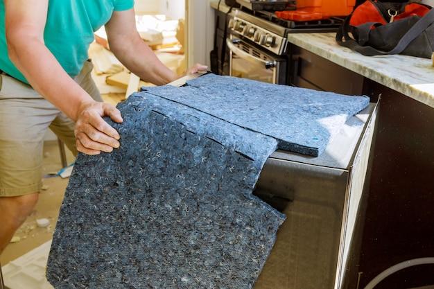 Męski technik naprawia zmywarka do naczyń w kuchni