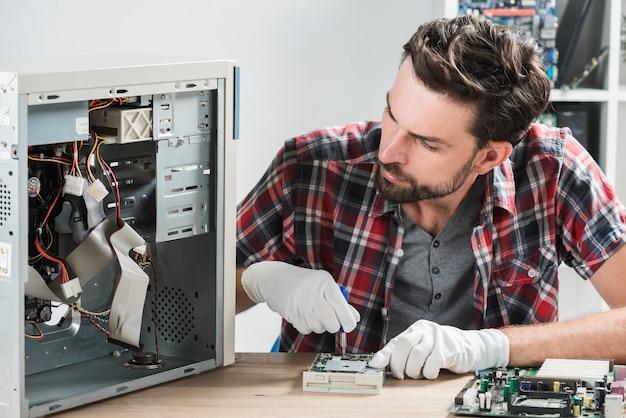 Męski technik pracuje na łamanym komputerze