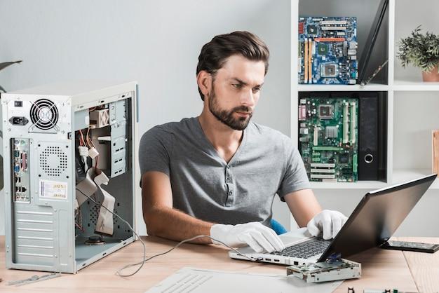 Męski technik używa laptop w warsztacie