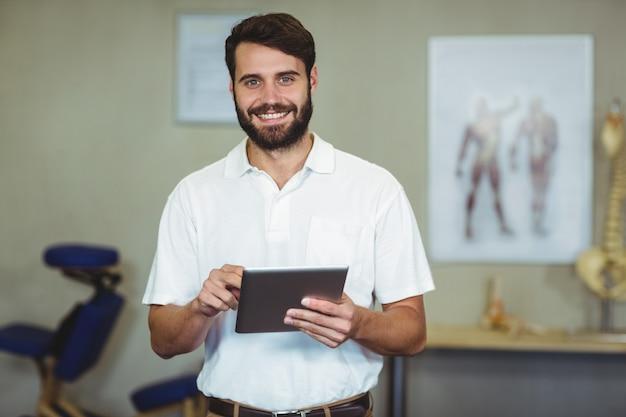 Męski terapeuta trzyma cyfrową pastylkę w klinice