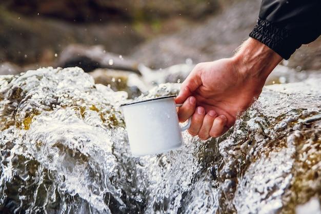 Męski turysta niosący metalowy kubek na tle rozmytych rzek.