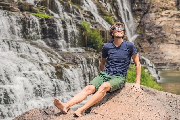 Męski turysta, turysta na powierzchni amazing pongour waterfall jest znany i najpiękniejszy z jesieni w wietnamie